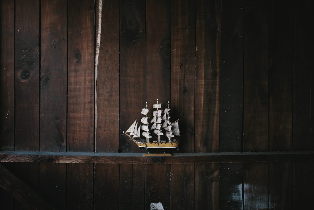 A model ship figurine on a wooden shelf