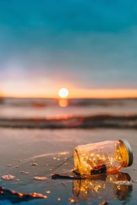 true happiness is not the absence of problems it is the ability to deal with them mason jar with lights on the beach