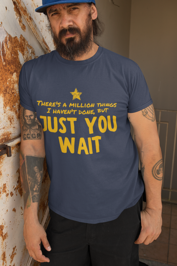 t shirt mockup featuring a bearded man leaning against a rusty wall 32841